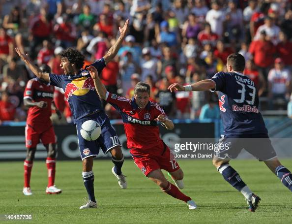 Logan Pause of the Chicago Fire pushes the ball between a complaining Mehdi Ballouchy and Kenny Cooper of the New York Red Bulls during an MLS match...