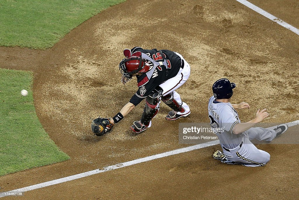 Logan Schafer #22 of the Milwaukee Brewers safely slides in to score a run past catcher Miguel Montero #26 of the Arizona Diamondbacks during the first inning of the MLB game at Chase Field on July 14, 2013 in Phoenix, Arizona. The Brewers defeated the Diamondbacks 5-1.