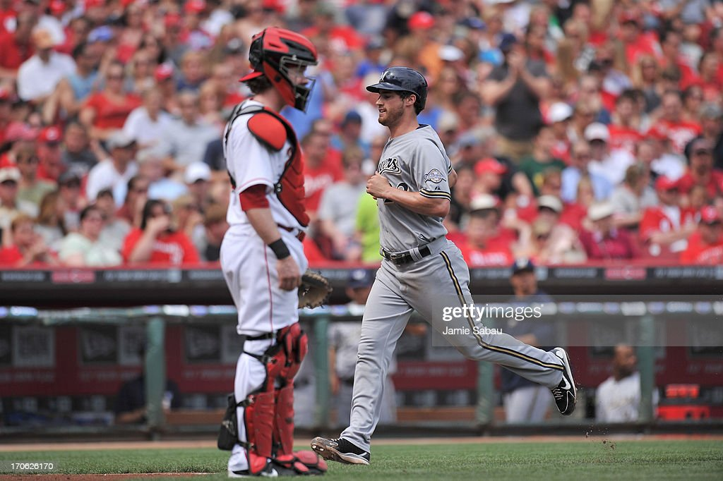 Logan Schafer #22 of the Milwaukee Brewers scores in the second inning past catcher Ryan Hanigan #29 of the Cincinnati Reds after a sacrifice fly at Great American Ball Park on June 15, 2013 in Cincinnati, Ohio.