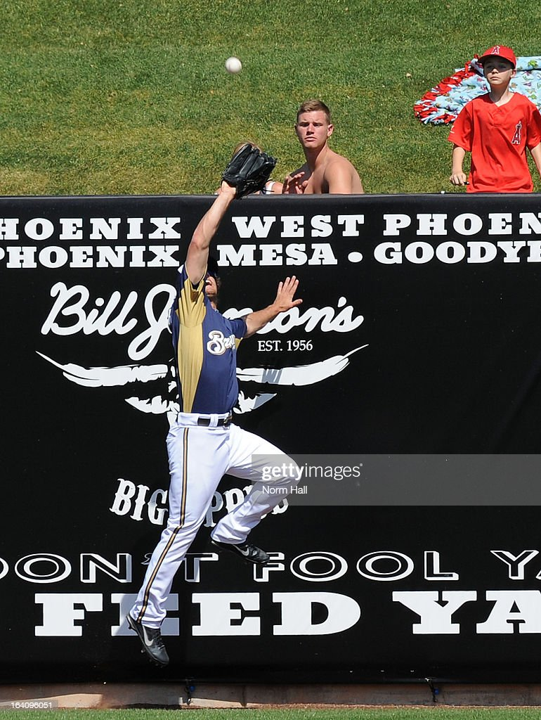 Logan Schafer #22 of the Milwaukee Brewers takes away an Albert Pujols home run by making a leaping catch at the wall against the Los Angeles Angels of Anaheim at Maryvale Baseball Park on March 19, 2013 in Maryvale, Arizona.