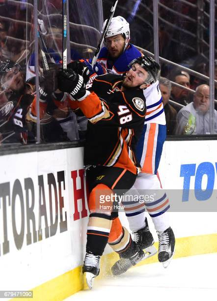 Logan Shaw of the Anaheim Ducks goes into the boards with Oscar Klefbom of the Edmonton Oilers during the first period in Game Five of the Western...