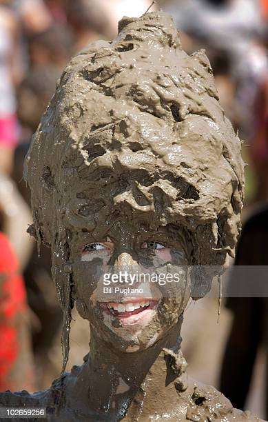 Logan Sibel age 12 of Redford Michigan gets some relief from the heat by playing in a gigantic lake of mud at the annual Mud Day event July 6 2010 in...