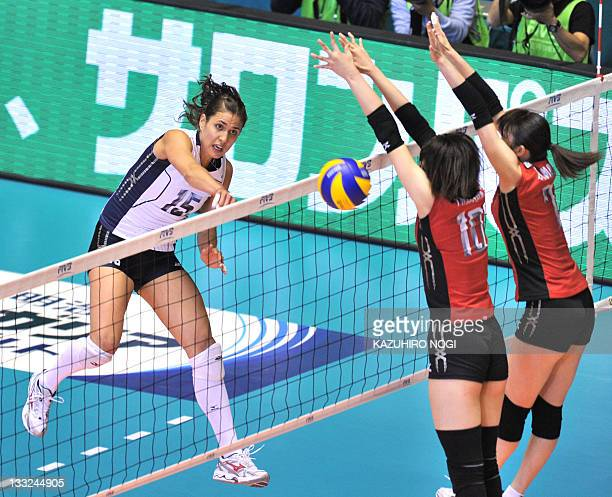 Logan Tom of the US spikes the ball past Japanese players Nana Iwasaka and Mai Yamaguchi during their match at the World Cup women's volleyball...