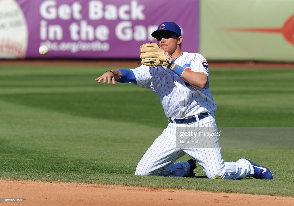 Logan Watkins #74 of the Chicago Cubs makes a throw from his knees against the Arizona Diamondbacks at Hohokam Stadium on March 1, 2013 in Mesa, Arizona.