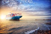 Logistics and transportation of Container Cargo ship in the ocean st sunset sky