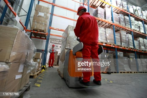 logistics - two workers working in storehouse with forklift loader : Stock Photo