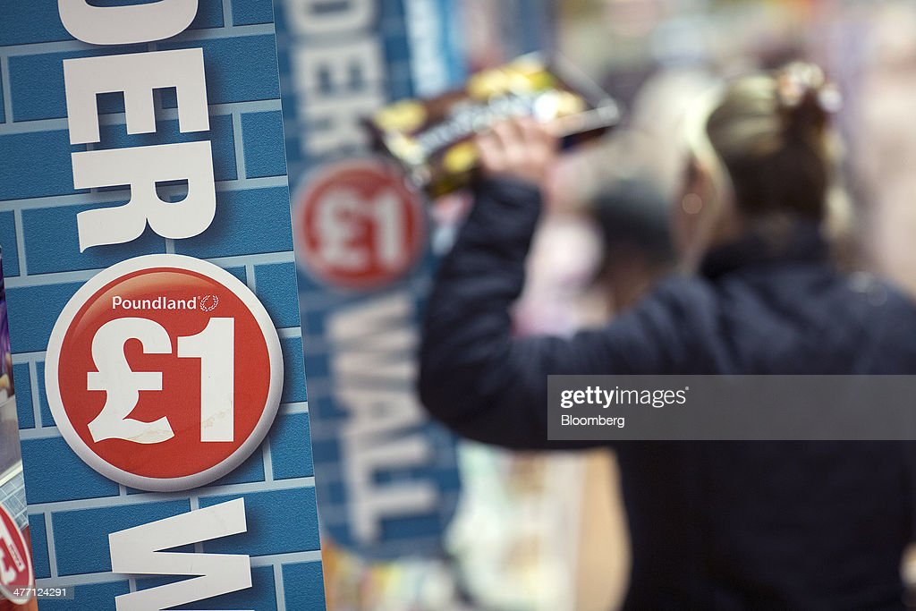 A logo advertising the cost of goods sits alongside a display shelf inside a Poundland discount store, operated by Poundland Group Plc in London, U.K., on Friday, March 7, 2014. Poundland Group Plc has demand for all the shares it is selling in an initial public offering that will value the U.K. discount retailer at as much as 750 million pounds ($1.3 billion), according to terms of the deal. Photographer: Simon Dawson/Bloomberg via Getty Images