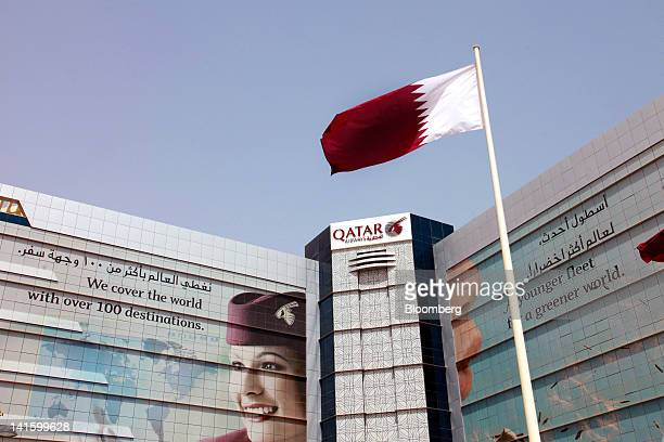 A logo and advertisments are seen outside the Qatar Airways Ltd airport buildings on Airport Road in Doha Qatar on Saturday March 17 2012 The country...