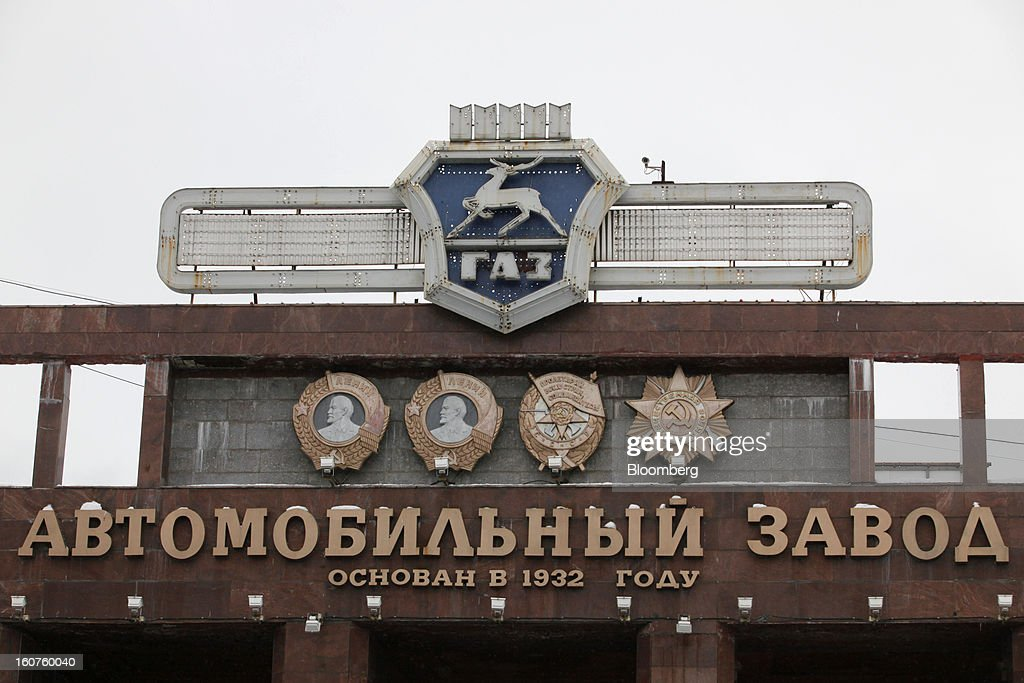 A logo and Soviet-era Lenin signs stand at the entrance to the GAZ Group automobile plant in Niznhy Novgorod, Russia, on Tuesday, Feb. 5, 2013. GAZ, which is controlled by Russian billionaire Oleg Deripaska, plans to make 30,000 Aveo sedans and hatchbacks a year at its plant in Nizhny Novgorod starting in mid-2012. Photographer: Alexander Zemlianichenko Jr./Bloomberg via Getty Images
