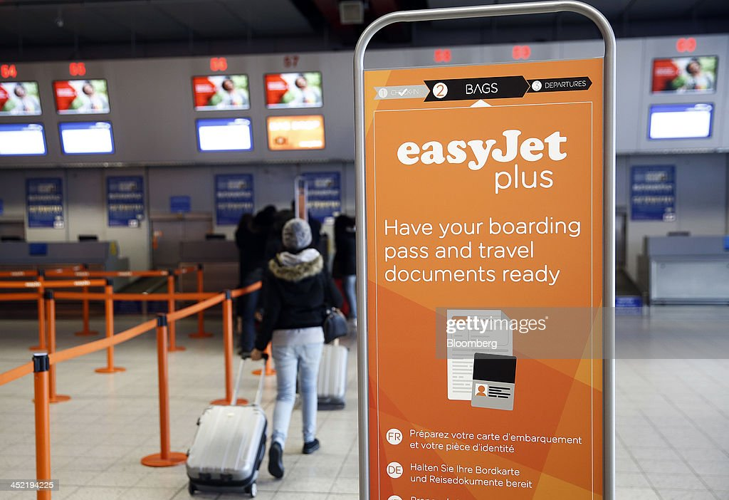 A logo for EasyJet Plus sits on a banner as customers arrive at EasyJet Plc's check-in desk at the airline's hub at London Luton Airport in Luton, U.K., on Tuesday, Nov. 26, 2013. Shares in International Consolidated Airlines Group SA (IAG) and EasyJet Plc climbed at least 2 percent, pushing a gauge of travel and leisure companies higher, as oil prices slid in reaction to Iran's nuclear deal with world powers. Photographer: Simon Dawson/Bloomberg via Getty Images