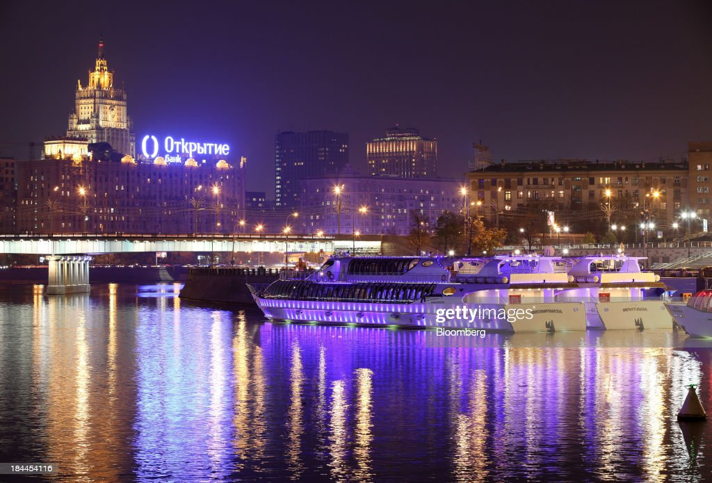 A logo for Otkrytie Bank OJSC stands illuminated at night beyond the River Moskva in Moscow, Russia, on Thursday, Oct. 10, 2013. Tinkoff Credit Systems Bank, operated by TCS Group Holding Plc, is valued at $2.5b to $3b for London IPO, which reflects P/E multiple of 9.5 to 11.4, Vedomosti reports, citing unidentified people familiar with offering documents. Photographer: Andrey Rudakov/Bloomberg via Getty Images