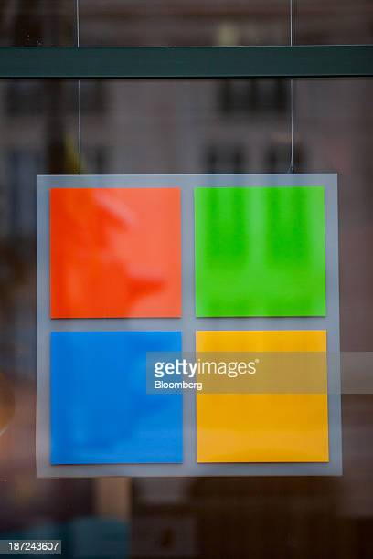 A logo for the Windows operating system hangs on display in a window of Microsoft Corp's new store in Berlin Germany on Thursday Nov 7 2013 Microsoft...