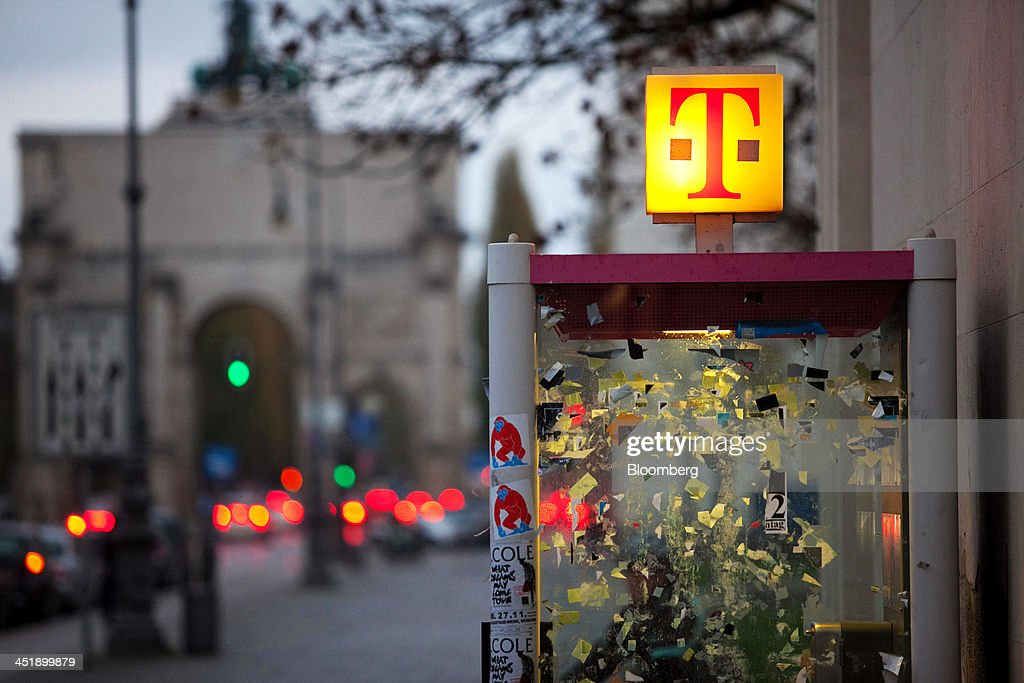 A logo for T-Mobile, operated by Deutsche Telekom AG, sits illuminated on top of a fixed-line telephone box in Munich, Germany, on Sunday, Nov. 24, 2013. In Germany, Europe's biggest economy, annual consumer prices increased 1.2 percent in October. Photographer: Krisztian Bocsi/Bloomberg via Getty Images