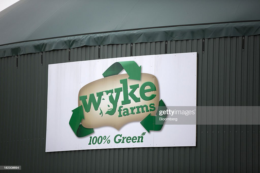 A logo for Wyke Farms is seen on a biogas container at Wyke Farms Ltd., in Bruton, U.K., on Friday, Sept. 27, 2013. Wyke Farms, the U.K.'s largest family-owned cheese maker and milk processor, has started using waste from its cows and pigs to generate clean power and help shave as much as 1 million pounds ($1.6 million) a year off its energy bills. Photographer: Simon Dawson/Bloomberg via Getty Images