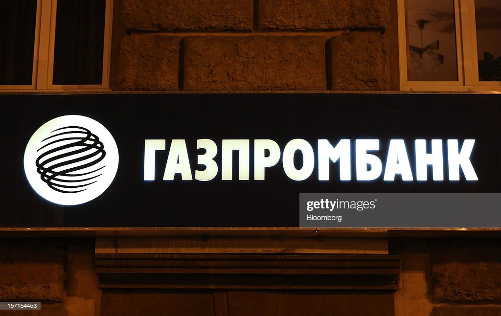 A logo hangs illuminated outside an OAO Gazprombank branch in Moscow, Russia, on Wednesday, Nov. 28, 2012. Bank Rossii proposes government create rule limiting increases of budget funds held at central bank, RIA Novosti reports, citing First Deputy Chairman Alexey Ulyukayev. Photographer: Andrey Rudakov/Bloomberg via Getty Images