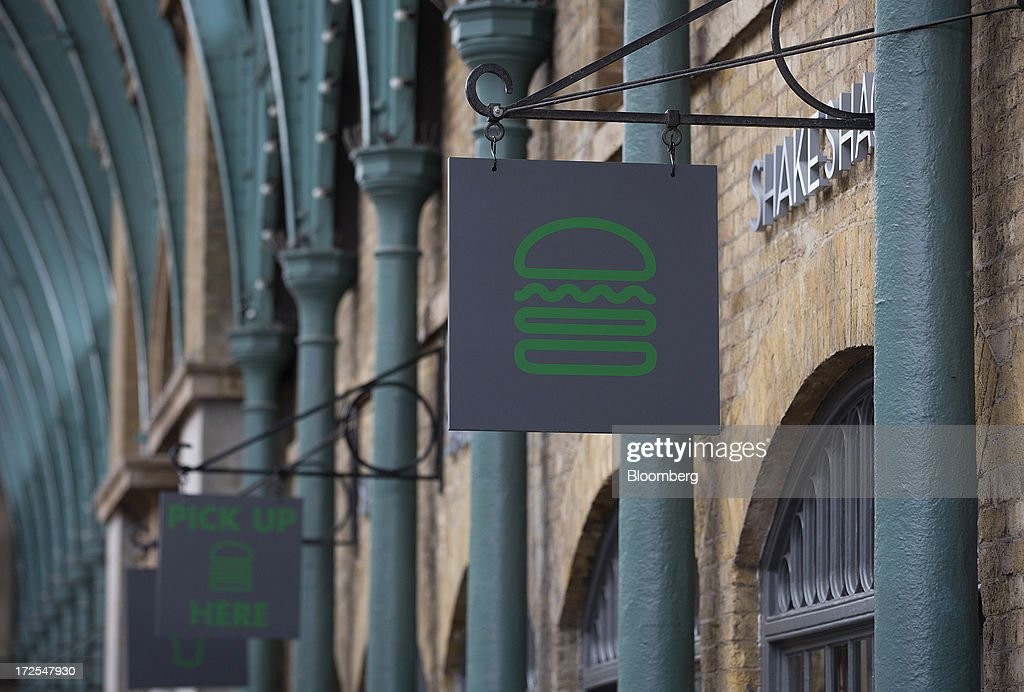 A logo hangs on a sign outside Shake Shack's new burger restaurant in London, U.K., on Tuesday, July 2, 2013. Shake Shack, opening in London's Covent Garden this week, started as a hotdog cart in New York's Madison Square Park, and has outlets in six U.S. states as well as in the Middle East and Turkey. Photographer: Simon Dawson/Bloomberg via Getty Images