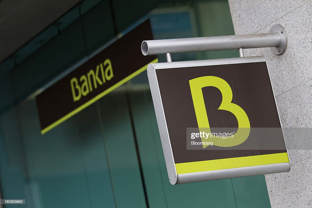 A logo hangs on display outside a Bankia SA bank branch in Madrid, Spain, on Thursday, Feb. 28, 2013. BFA-Bankia Chairman Jose Ignacio Goirigolzarri said a balance sheet clean-up that inflicted a 21.2 billion-euro ($27.6 billion) after-tax loss last year will set the Spanish banking group on course to repay state aid. Photographer: Angel Navarrete/Bloomberg via Getty Images
