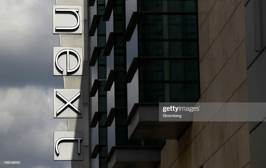 A logo hangs on display outside a Next Plc store in Manchester, U.K., on Monday, April 1, 2013. U.K. retail sales unexpectedly stagnated in March in a sign that consumer spending remains under pressure from higher energy bills and weak wage growth. Photographer: Paul Thomas/Bloomberg via Getty Images
