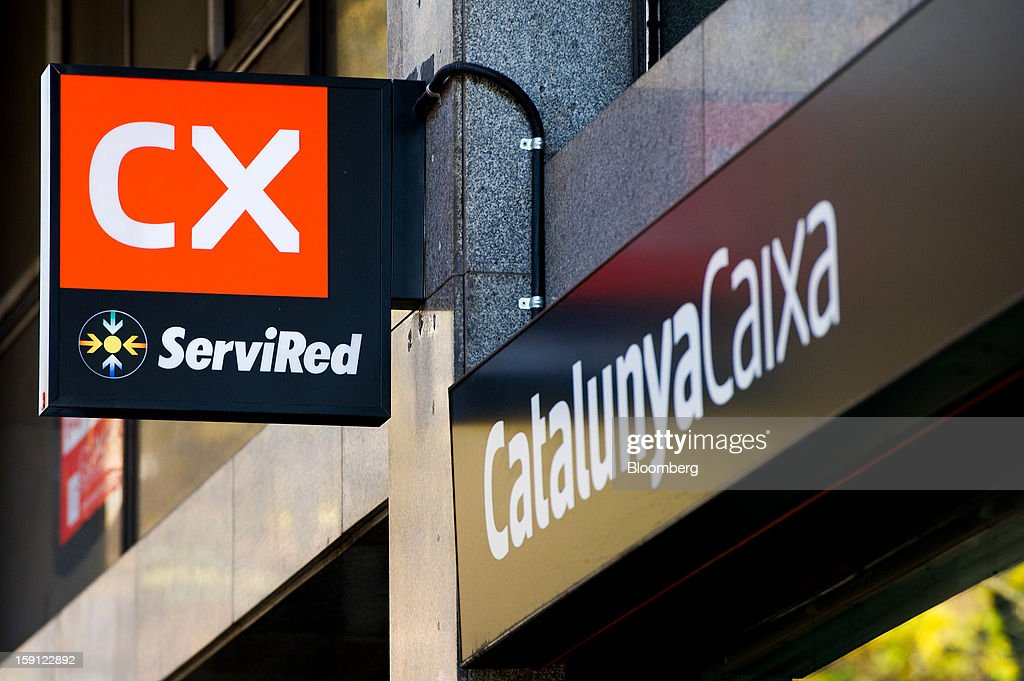 A logo hangs outside a CatalunyaCaixa bank branch in Barcelona, Spain, on Tuesday, Jan. 8, 2013. Banco Santander SA, Spain's biggest lender, will offer 263 million euros ($345 million) in stock to buy out minority investors in its Banco Espanol de Credito SA retail unit and close 700 local branches to cut costs. Photographer: David Ramos/Bloomberg via Getty Images