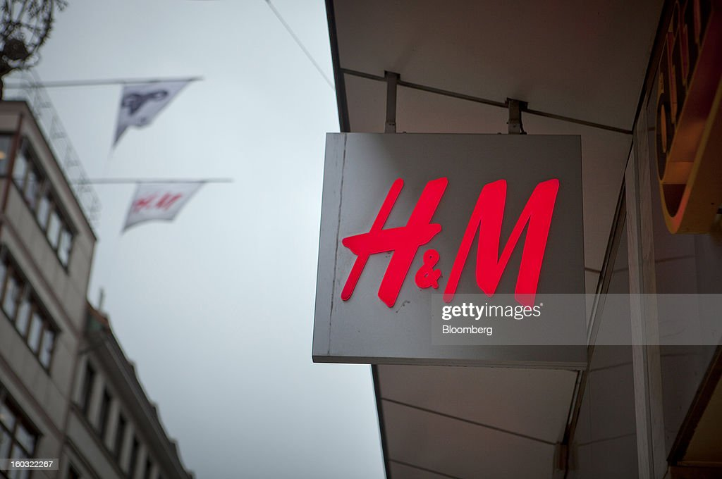 A logo hangs outside a Hennes & Mauritz AB (H&M) store in Stockholm, Sweden, on Tuesday, Jan. 29, 2013. Hennes & Mauritz AB, Europe's second-largest clothing retailer, reported sales growth that beat analysts' estimates for a second consecutive month as the chain offered markdowns in advance of the Christmas holiday. Photographer: Casper Hedberg/Bloomberg via Getty Images