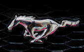 A logo is attached to the grill of a Ford Mustang sitting on the lot at Joyce Ford June 6 2007 in Chicago Illinois The Mustang helped Ford edge out...