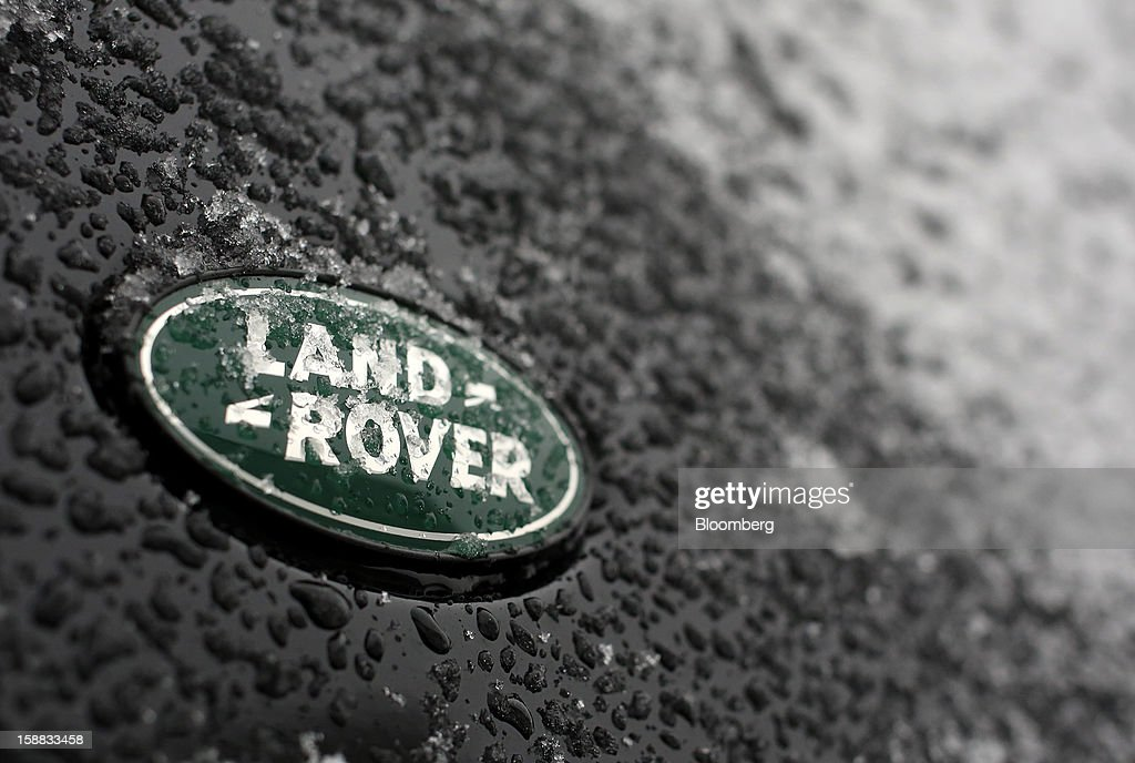 A logo is seen beneath ice on the panel work of a Land Rover automobile outside a Jaguar Land Rover auto dealership in Moscow, Russia, on Thursday, Dec. 27, 2012. Tata Motors Ltd.'s Jaguar Land Rover luxury unit signed a letter of intent with Saudi Arabia's government to study the feasibility of setting up a factory to build its models locally. Photographer: Andrey Rudakov/Bloomberg via Getty Images