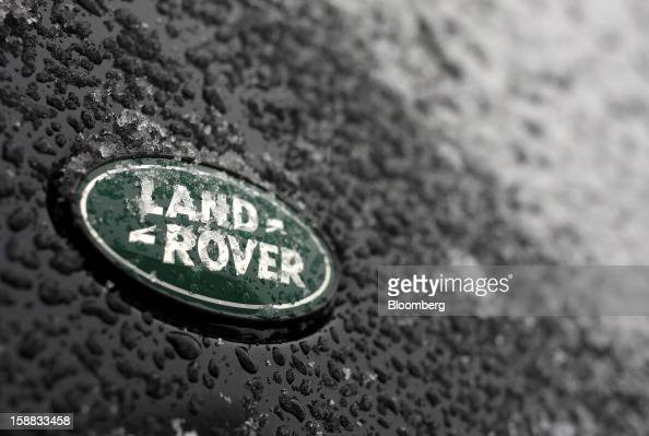 A logo is seen beneath ice on the panel work of a Land Rover automobile outside a Jaguar Land Rover auto dealership in Moscow Russia on Thursday Dec...