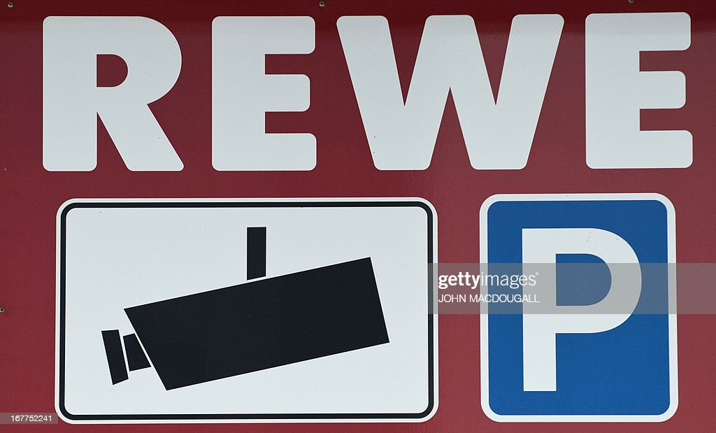A logo of German supermarket chain REWE appears on a sign indicating that the parking area of the supermarket is under video surveillance, in Berlin April 29, 2013. Employees were temporarily monitored illegally at Penny south, a discount subsidiary of Rewe, the company admitted on April 29, 2013. AFP PHOTO / JOHN MACDOUGALL