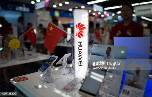 A logo of Huawei Technologies Co Ltd is seen next to a Chinese flag in an electronic shop in Shanghai on October 1 2014 The founder of Chinese...