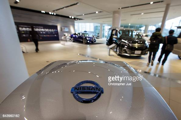 A logo of Nissan is seen on top of a hybrid engine on display at the company's global headquarters showroom on February 23 2017 in Yokohama Japan...