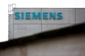 A logo of Siemens is seen on the top of the company plant on February 12 2014 in Vienna Austria Siemens produce masstransit rail vehicles and...