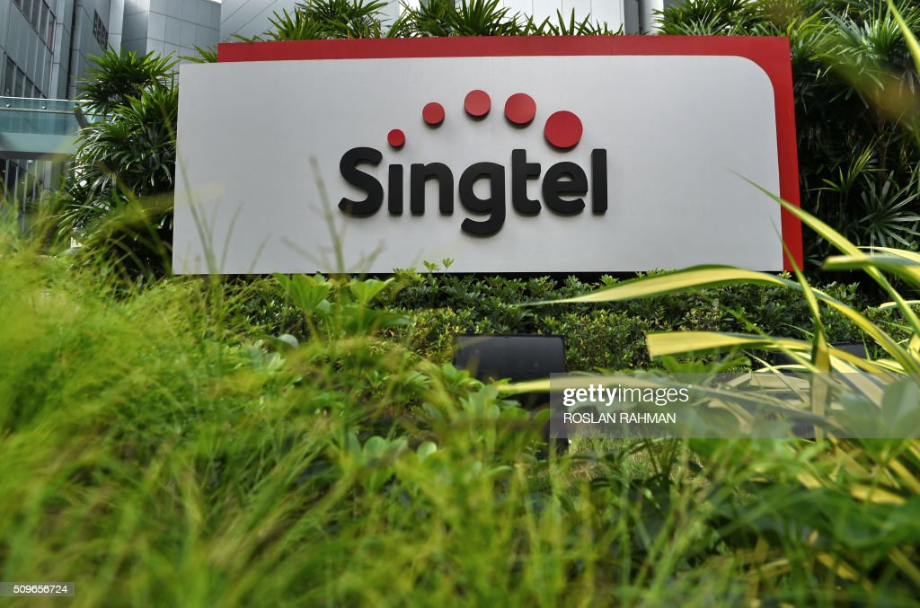 A logo of Singapore Telecommunications (Singtel) is seen outside its building in Singapore on February 12, 2016. Singtel reported a 1.7 per cent fall in third-quarter net profit of 683 million US dollar for the three months ended December, compared with 694 million US dollar a year ago, as adverse currency movements and investments offset growing mobile data usage by its customers. AFP PHOTO / ROSLAN RAHMAN / AFP / ROSLAN RAHMAN