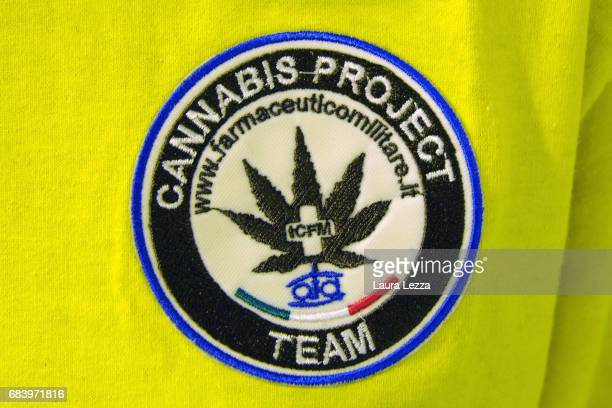 A logo of the Cannabis Project is displayed on the shirt of a grower employee in a greenhouse at the Italian Army at Stabilimento Chimico...