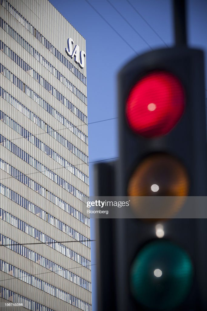 A logo outside the offices of SAS AB airlines is seen beyond a road traffic signal in central Copenhagen, Denmark, on Monday, Nov. 19, 2012. Denmark's two-year yields sank to the lowest in almost three months in Copenhagen trading as Europe's debt crisis continues to drive investors north. Photographer: Linus Hook/Bloomberg via Getty Images