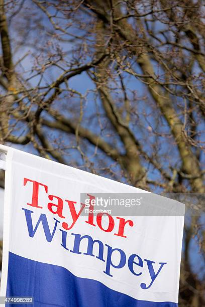 A logo sits a banner as it hangs outside newly constructed homes at a Taylor Wimpey Plc residential housing construction site in Taplow UK on...