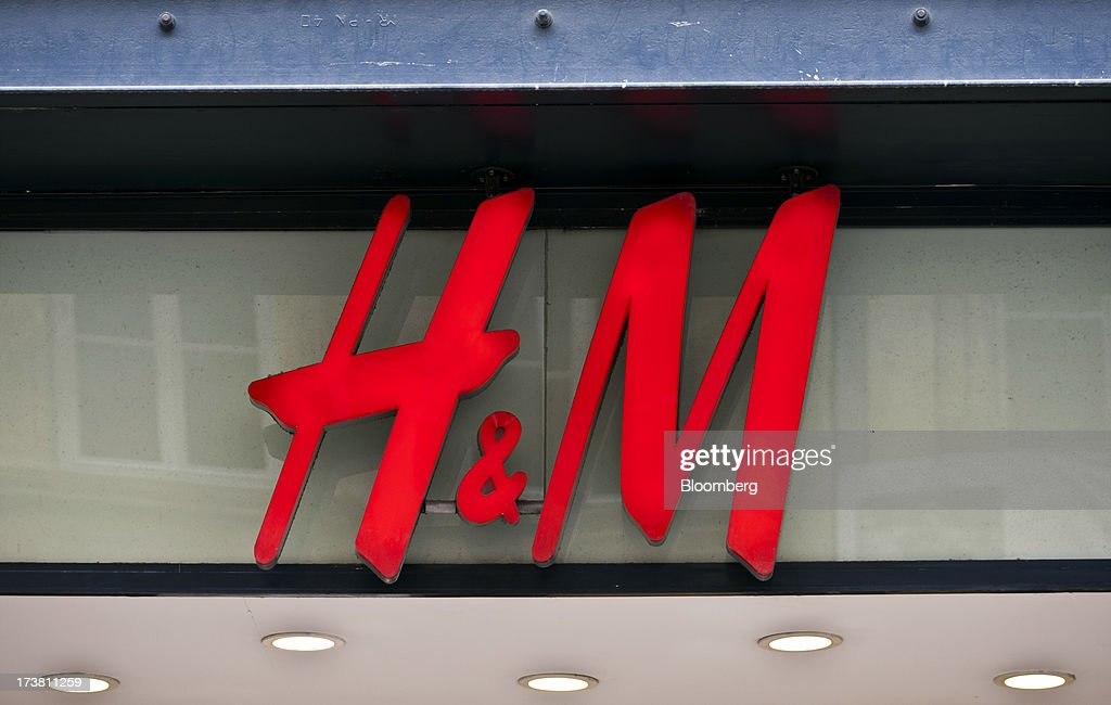 A logo sits above a store operated by Hennes & Mauritz AB (H&M) in Bordeaux, France, on Wednesday, July 17, 2013. Austerity measures and rising unemployment are restraining consumer spending in Europe, while retailers including Groupe Auchan SA and Casino Guichard-Perrachon SA are competing more aggressively on price. Photographer: Balint Porneczi/Bloomberg via Getty Images