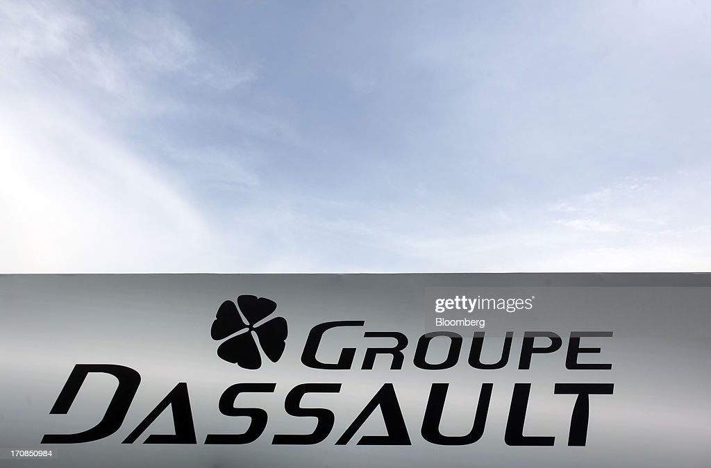 A logo sits above the Dassault Aviation SA's display booth on the second day of the Paris Air Show in Paris, France, on Tuesday, June 18, 2013. The 50th International Paris Air Show is the world's largest aviation and space industry show, and takes place at Le Bourget airport June 17-23. Photographer: Balint Porneczi/Bloomberg via Getty Images