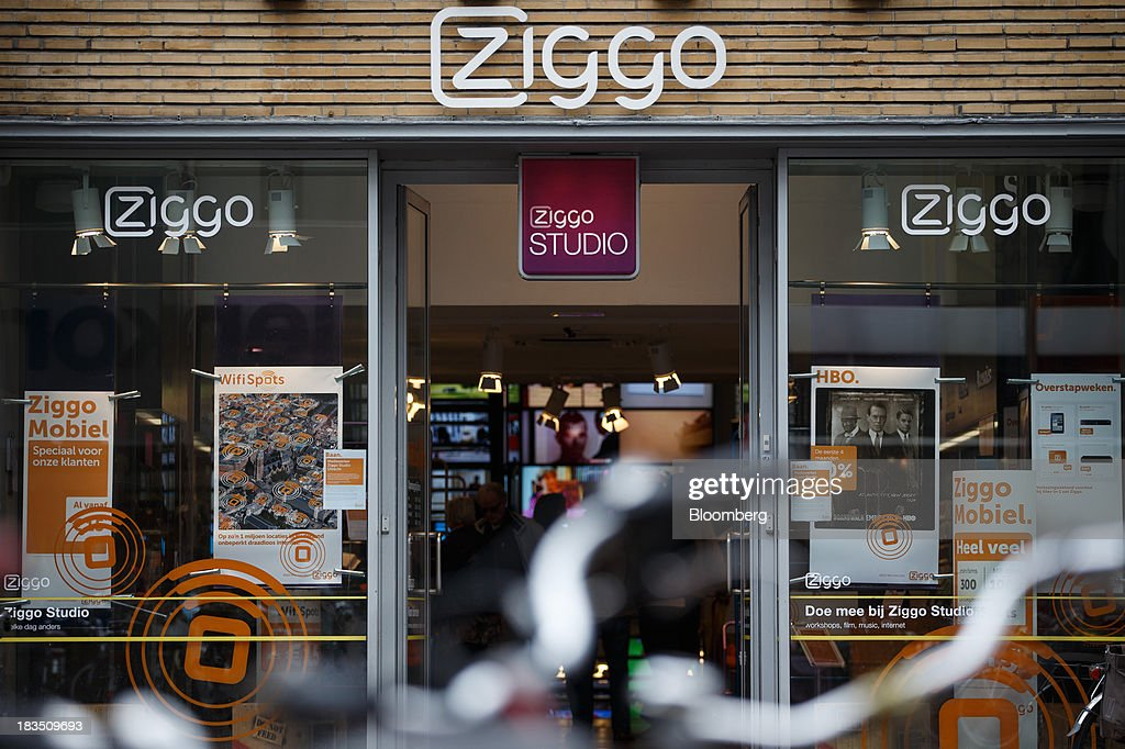 A logo sits above the entrance to a Ziggo NV store in Utrecht, Netherlands, on Friday, Oct. 4, 2013. Cable-TV provider Ziggo, which is 28.5 percent owned by Liberty Global Plc, is pushing into the Dutch mobile market with low-priced packages, following a playbook pioneered by French discount operator Iliad SA. Photographer: Jasper Juinen/Bloomberg via Getty Images
