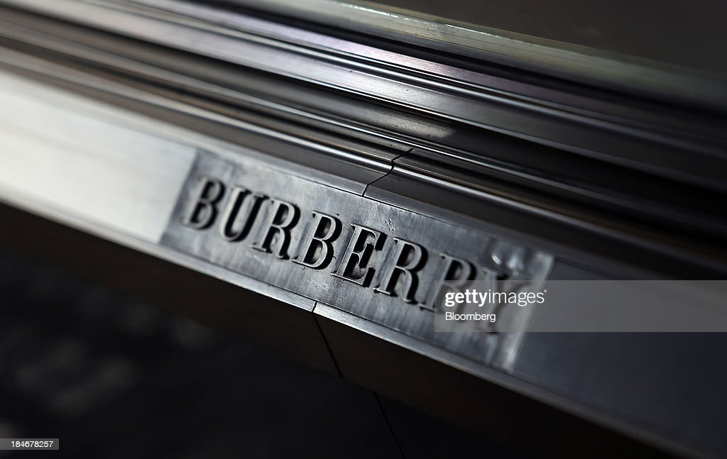 A logo sits beneath a window display at Burberry Group Plc's luxury clothing store on Regent Street in London, U.K., on Tuesday, Oct. 15, 2013. Burberry named Christopher Bailey as chief executive officer to succeed Angela Ahrendts who will leave in 2014 to work as a senior vice president at Apple Inc. Photographer: Chris Ratcliffe/Bloomberg via Getty Images