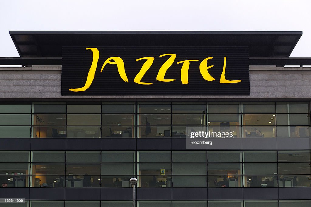 A logo sits illuminated above offices at the offices of Jazztel Plc in Alcobendas, Spain, on Thursday, April 4, 2013. Jazztel almost doubled its share of the Spanish broadband market from 2009 to 2012 as it focused mostly on the fixed-telephone business through a reliable and affordable product that has gained popularity among debt-strapped Spaniards. Photographer: Angel Navarrete/Bloomberg via Getty Images