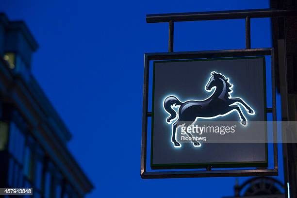 A logo sits illuminated at dawn outside a Lloyds Bank branch operated by Lloyds Banking Group Plc in London UK on Monday Oct 27 2014 'Lloyds fared...