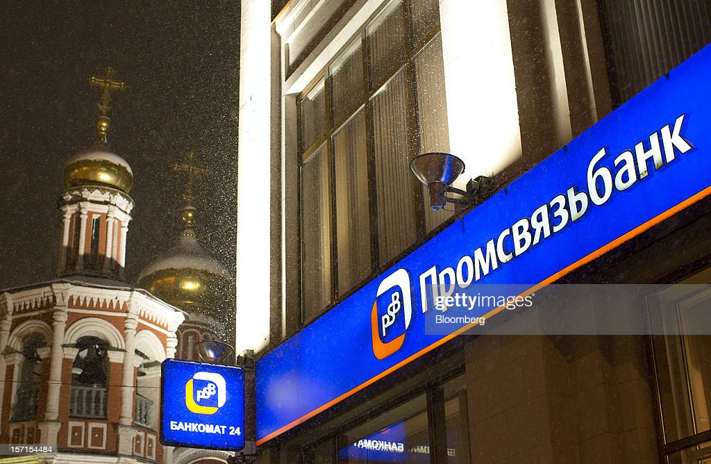 A logo sits illuminated outside a branch of OAO Promsvyazbank near a Russian orthodox church in Moscow, Russia, on Wednesday, Nov. 28, 2012. Bank Rossii proposes government create rule limiting increases of budget funds held at central bank, RIA Novosti reports, citing First Deputy Chairman Alexey Ulyukayev. Photographer: Andrey Rudakov/Bloomberg via Getty Images