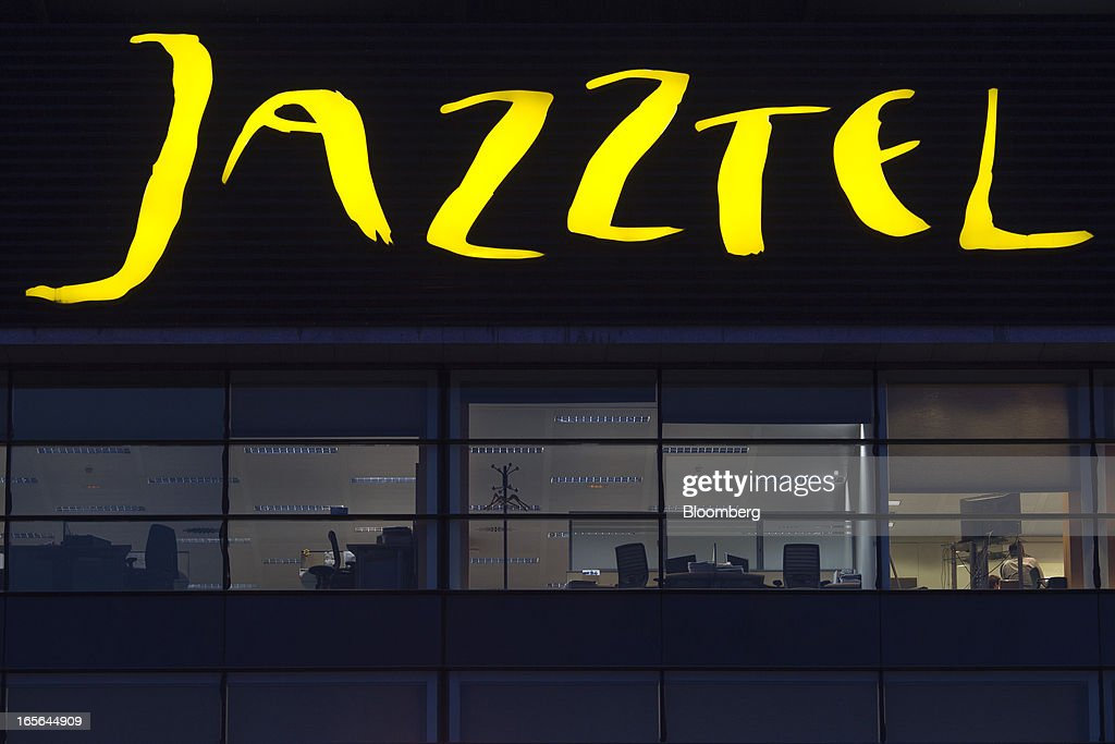 A logo sits illuminated outside the offices at the offices of Jazztel Plc in Alcobendas, Spain, on Thursday, April 4, 2013. Jazztel almost doubled its share of the Spanish broadband market from 2009 to 2012 as it focused mostly on the fixed-telephone business through a reliable and affordable product that has gained popularity among debt-strapped Spaniards. Photographer: Angel Navarrete/Bloomberg via Getty Images