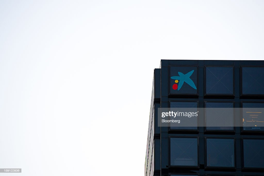 A logo sits in the office window of a CaixaBank SA bank branch in Barcelona, Spain, on Tuesday, Jan. 8, 2013. Banco Santander SA, Spain's biggest lender, will offer 263 million euros ($345 million) in stock to buy out minority investors in its Banco Espanol de Credito SA retail unit and close 700 local branches to cut costs. Photographer: David Ramos/Bloomberg via Getty Images