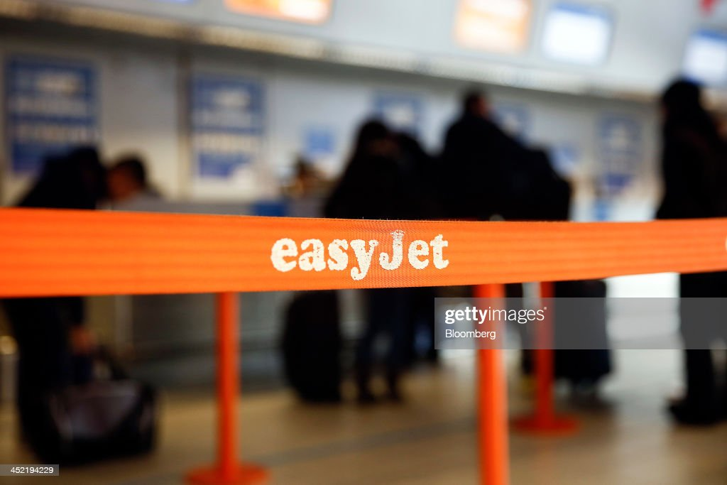 A logo sits on a barrier as customers queue at EasyJet Plc's check-in desks at the airline's hub at London Luton Airport in Luton, U.K., on Tuesday, Nov. 26, 2013. Shares in International Consolidated Airlines Group SA (IAG) and EasyJet Plc climbed at least 2 percent, pushing a gauge of travel and leisure companies higher, as oil prices slid in reaction to Iran's nuclear deal with world powers. Photographer: Simon Dawson/Bloomberg via Getty Images