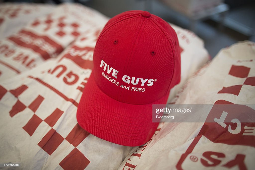 A logo sits on a baseball cap in the kitchen at U.S. burger restaurant chain Five Guys in London, U.K., on Tuesday, July 2, 2013. Five Guys, which is set to open its first U.K. store in Covent Garden on July 4, is a family outfit that started in Washington, D.C., in 1986, and has expanded to more than 1,000 locations in the U.S. and Canada. Photographer: Simon Dawson/Bloomberg via Getty Images