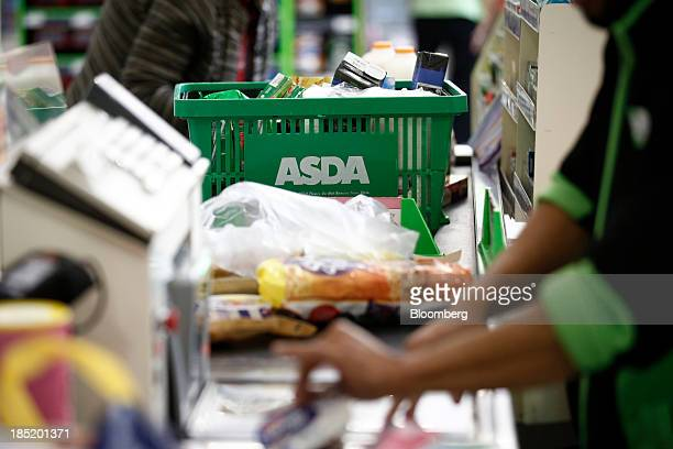 A logo sits on a customer's shopping basket on the conveyor belt of a checkout desk inside an Asda supermarket the UK retail arm of WalMart Stores...