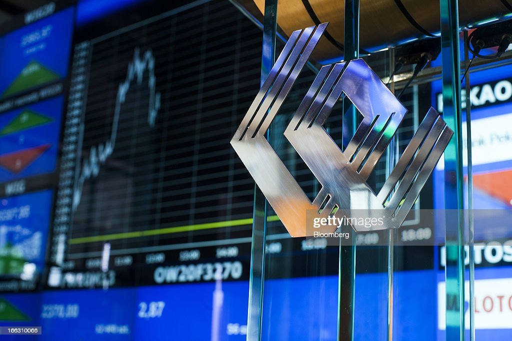 A WSE logo sits on a glass panel near an electronic display showing an index curve and financial data at the Warsaw Stock Exchange in Warsaw, Poland, on Thursday, April 11, 2013. Poland's central bank kept interest rates unchanged at a record-low 3.25 percent yesterday. Photographer: Bartek Sadowski/Bloomerg