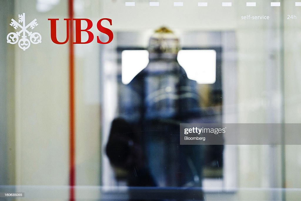 AG logo sits on a glass window as a customer uses an automated teller machine (ATM) in Geneva, Switzerland, on Sunday, Feb. 3, 2013. UBS AG will report fourth-quarter results for the 2012 financial year on Feb. 5. Photographer: Valentin Flauraud/Bloomberg via Getty Images