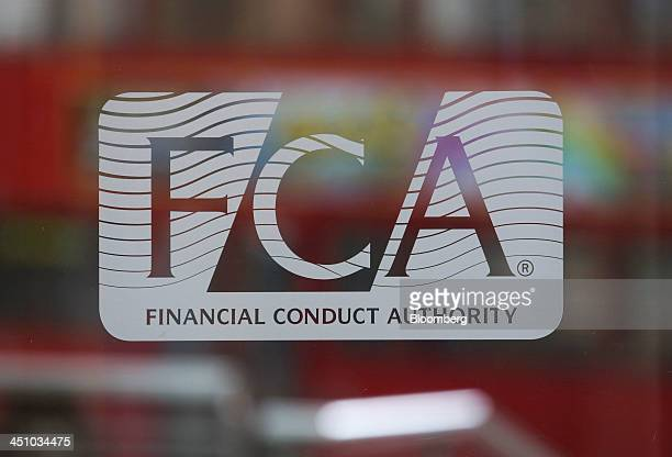 A logo sits on a revolving glass door at the headquarters of the Financial Conduct Authority in the Canary Wharf business district in London UK on...